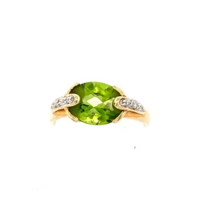 Yellow Peridot and Diamond Ring. 14k yellow gold with 2.5 carat oval Peridot and six round brilliant diamonds weighing a combined .04 carat.